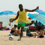 man-kicking-ball-on-beach